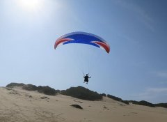 Dolphin Paragliding student above training dunes